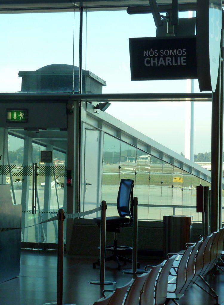 """Anzeige """"Nos somos Charlie"""" am Flughafen von Porto"""