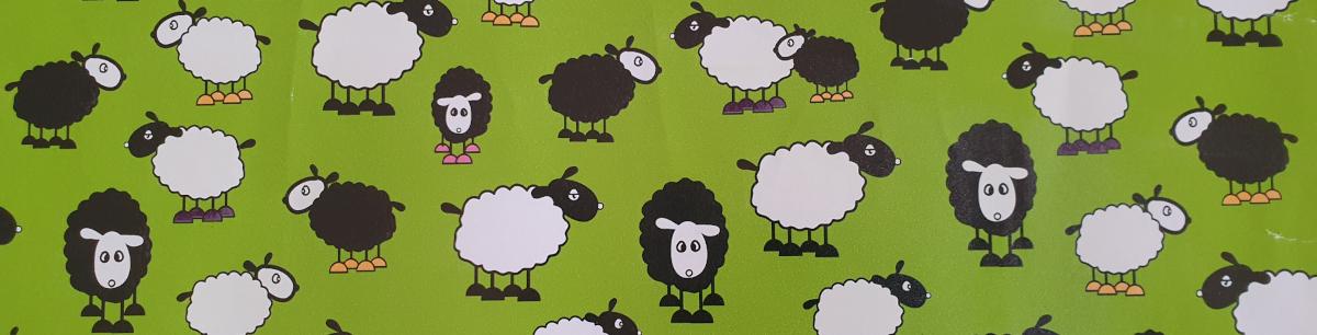 Geschenkpapier mit Schafen, davon viele schwarze Schafe